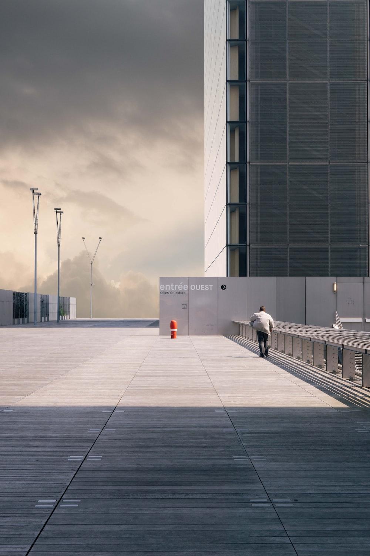 man walking on concrete pavement near building during daytime