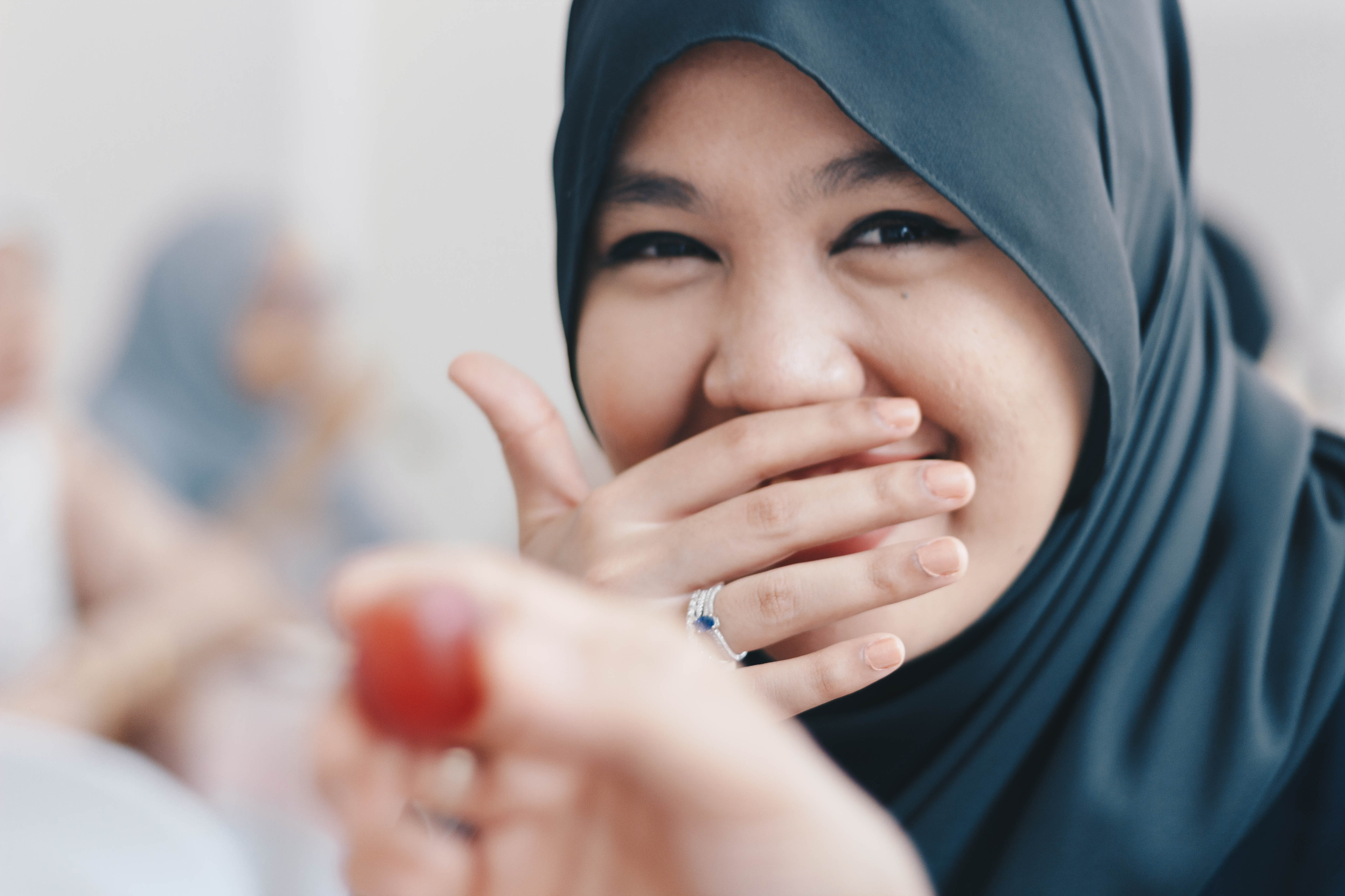 woman covering her mouth while laughing