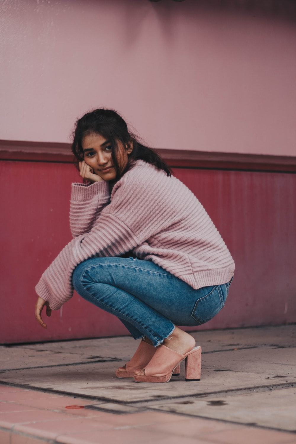 photography of woman in pink sweater and blue jeans docking