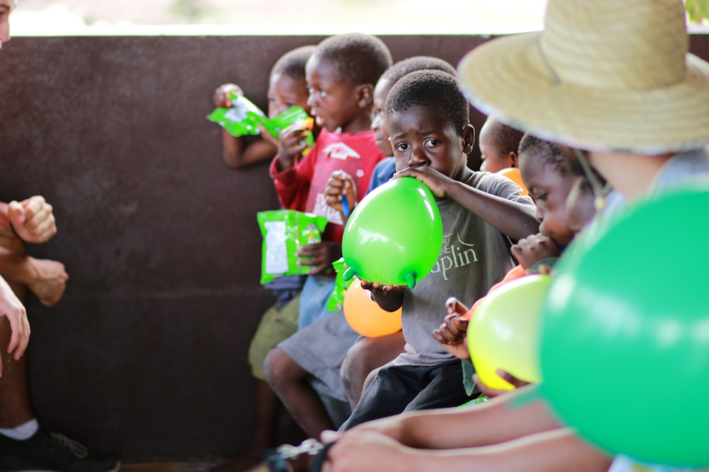 boy blowing green balloon