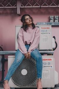 woman sitting near Toshiba air condenser