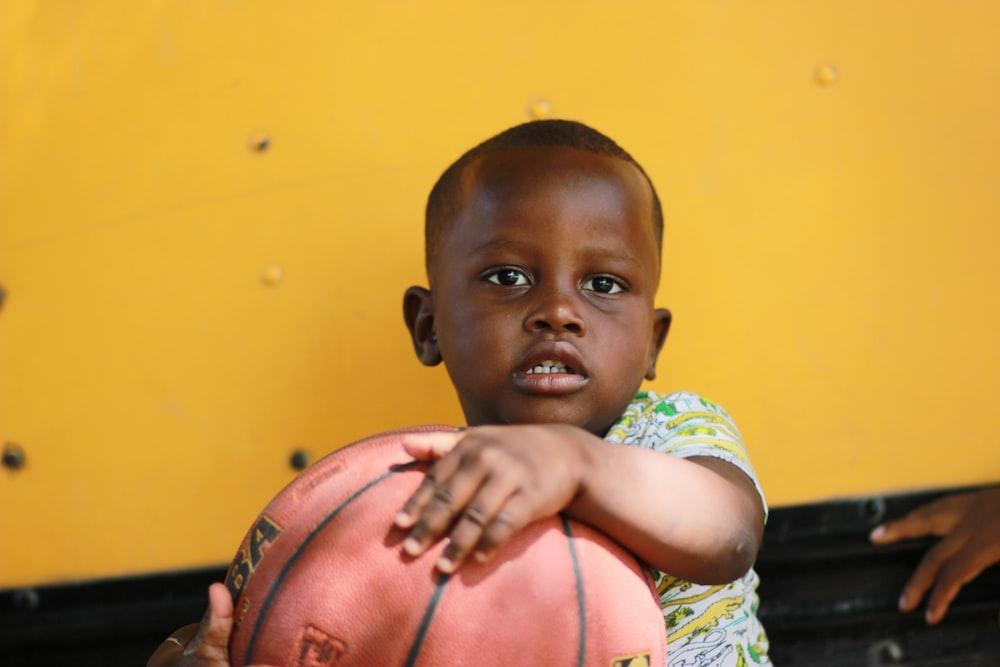 boy holding brown basketball