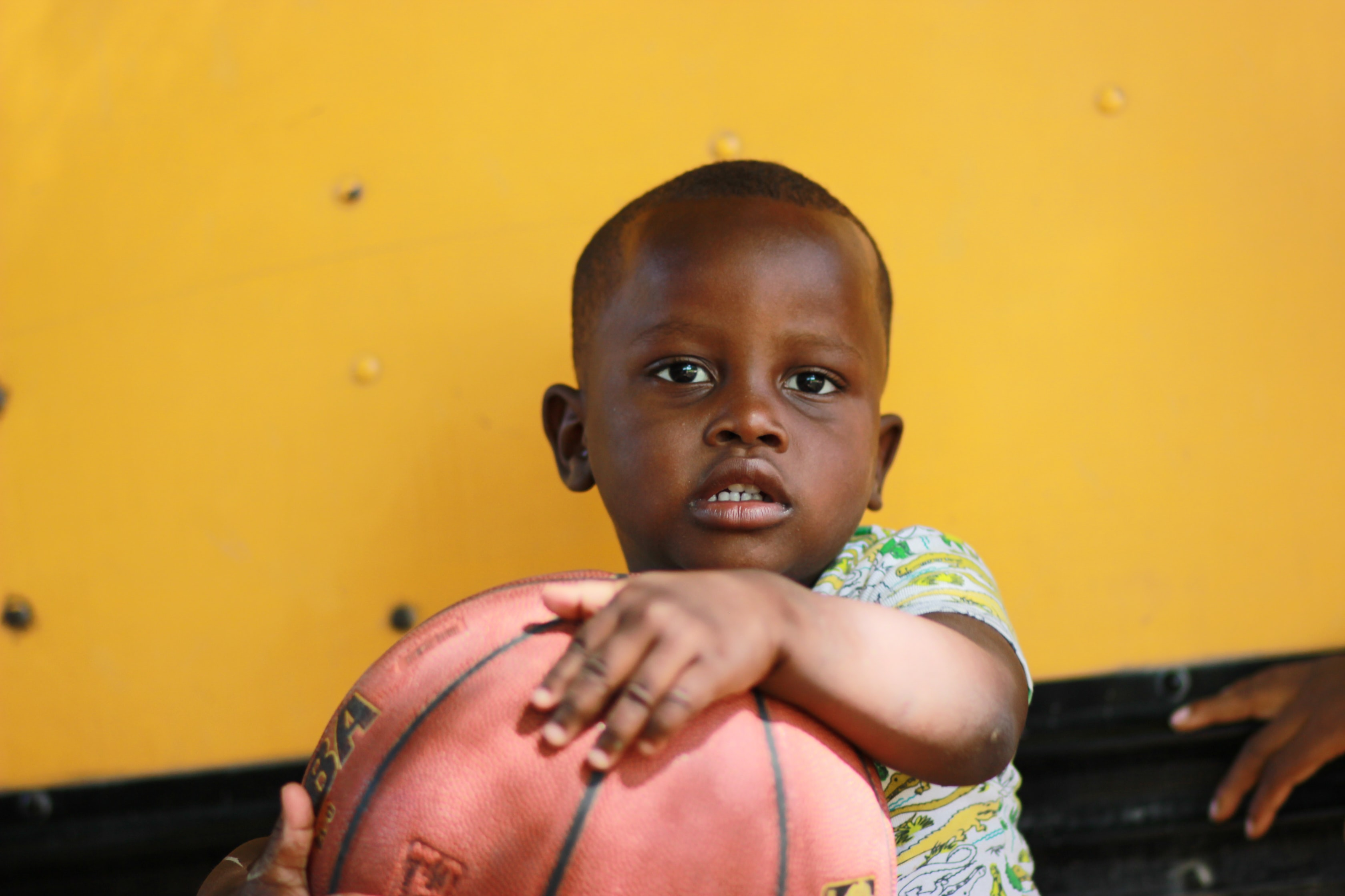 boy holding brown basketball