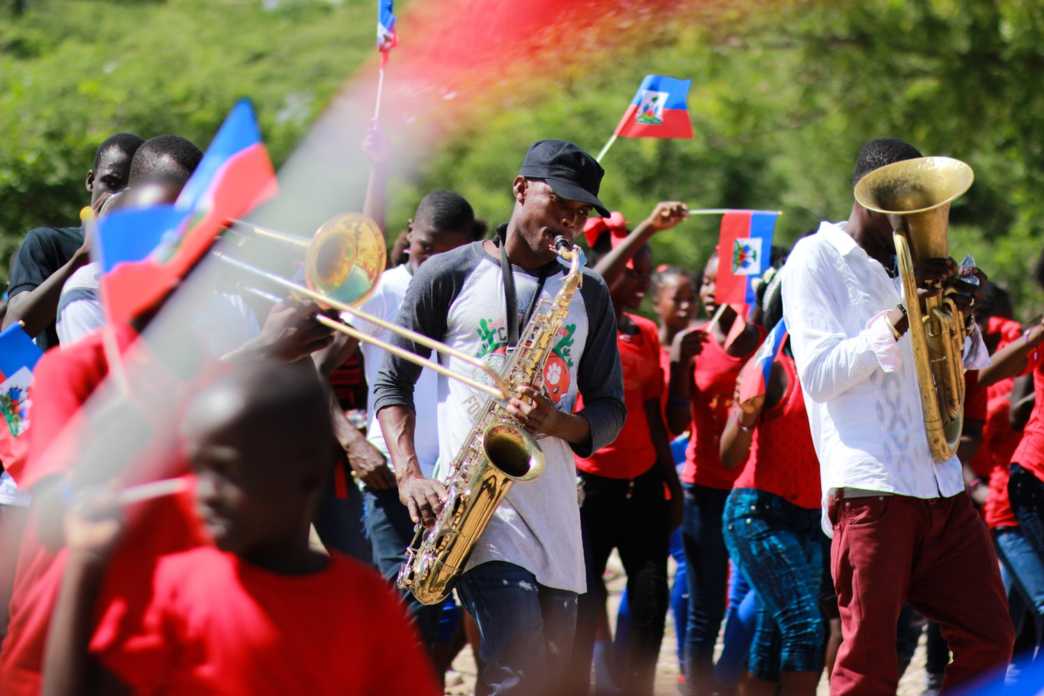 Haiti people are playing some instruments while others are waving their flags