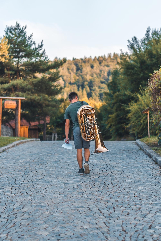 man carrying brass music instrument