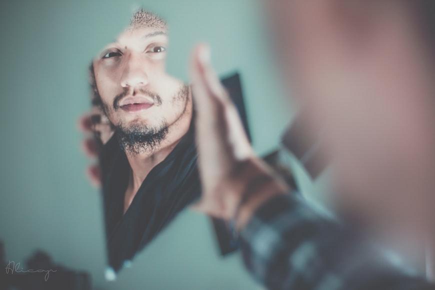 uomo che si riflette su un coccio di specchio