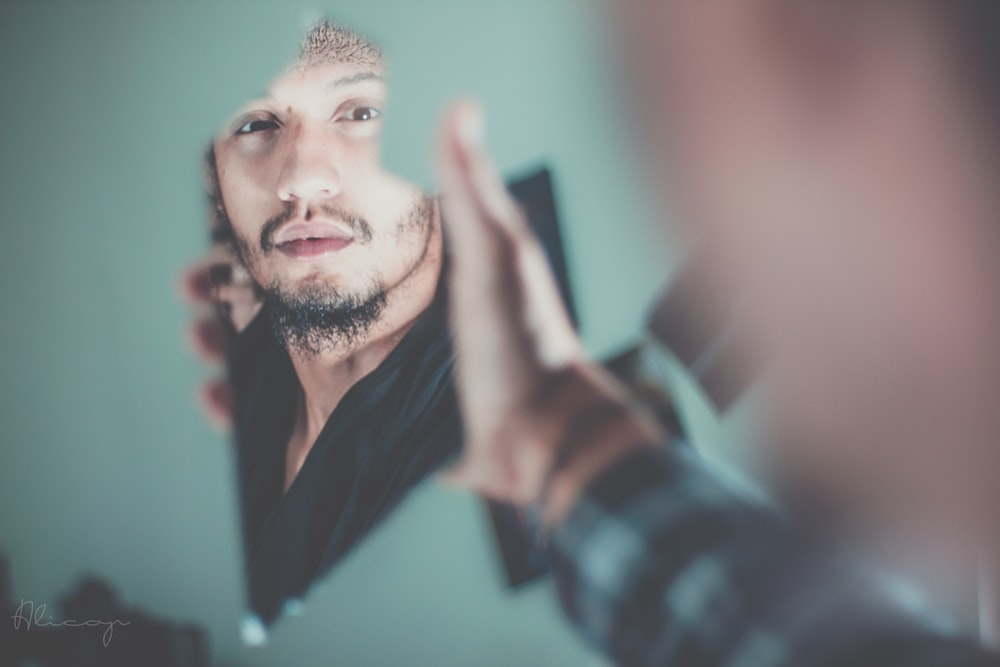 selective focus photography of man's reflection on a broken mirror