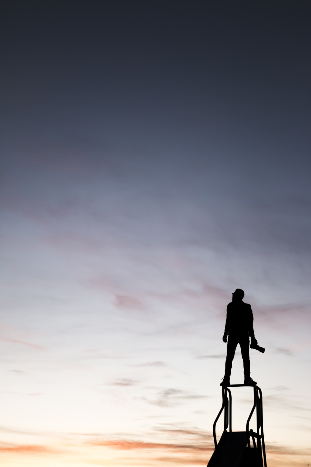silhouette of man standing on slide while holding camera