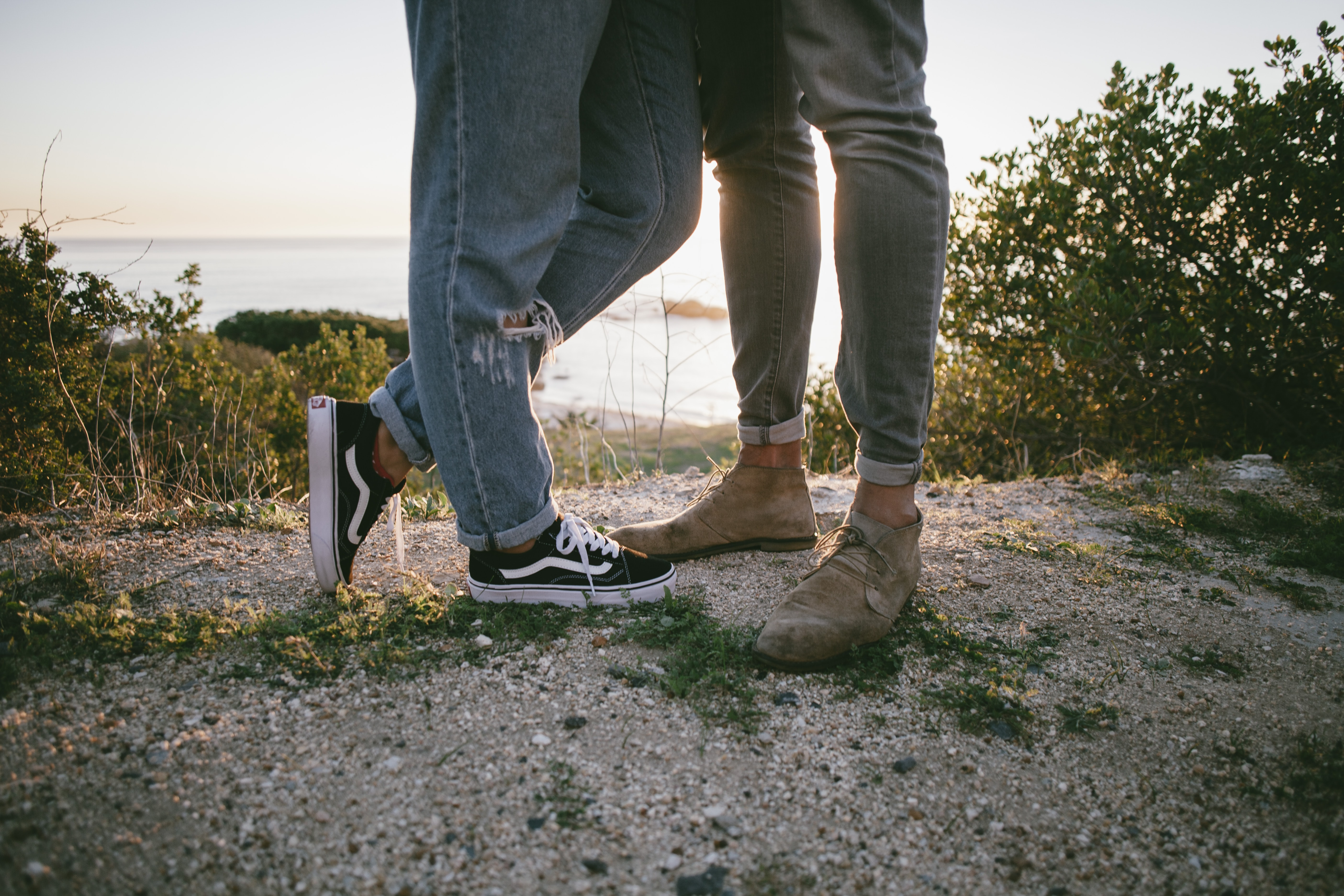 two persons standing on sand