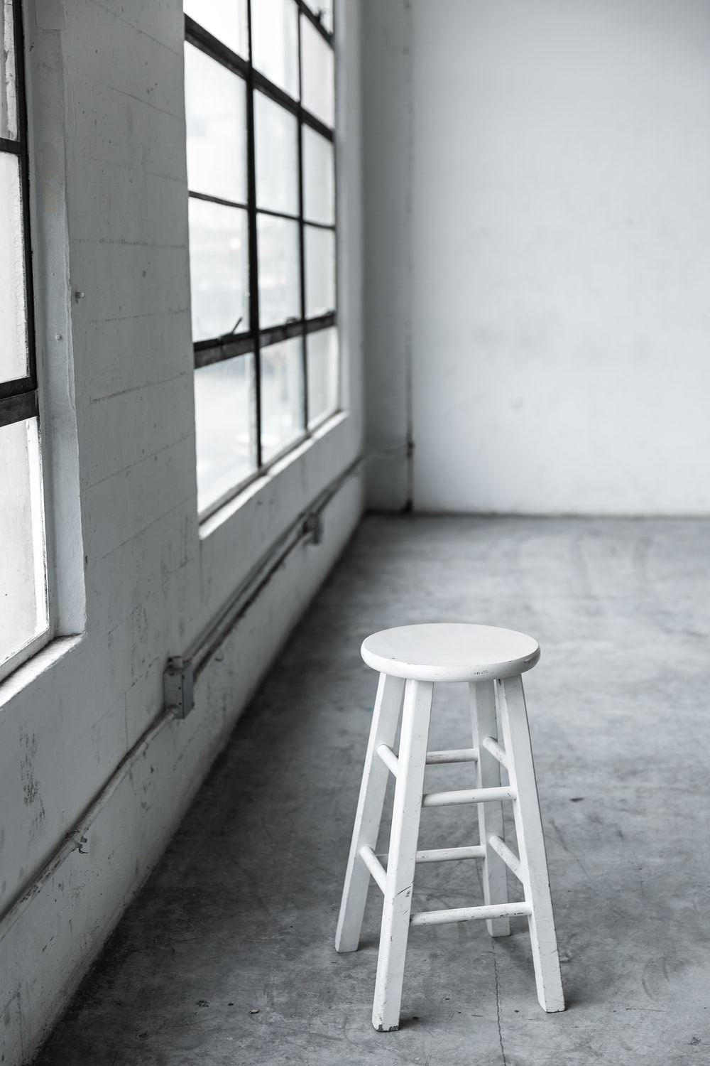 round white wooden stool near closed window