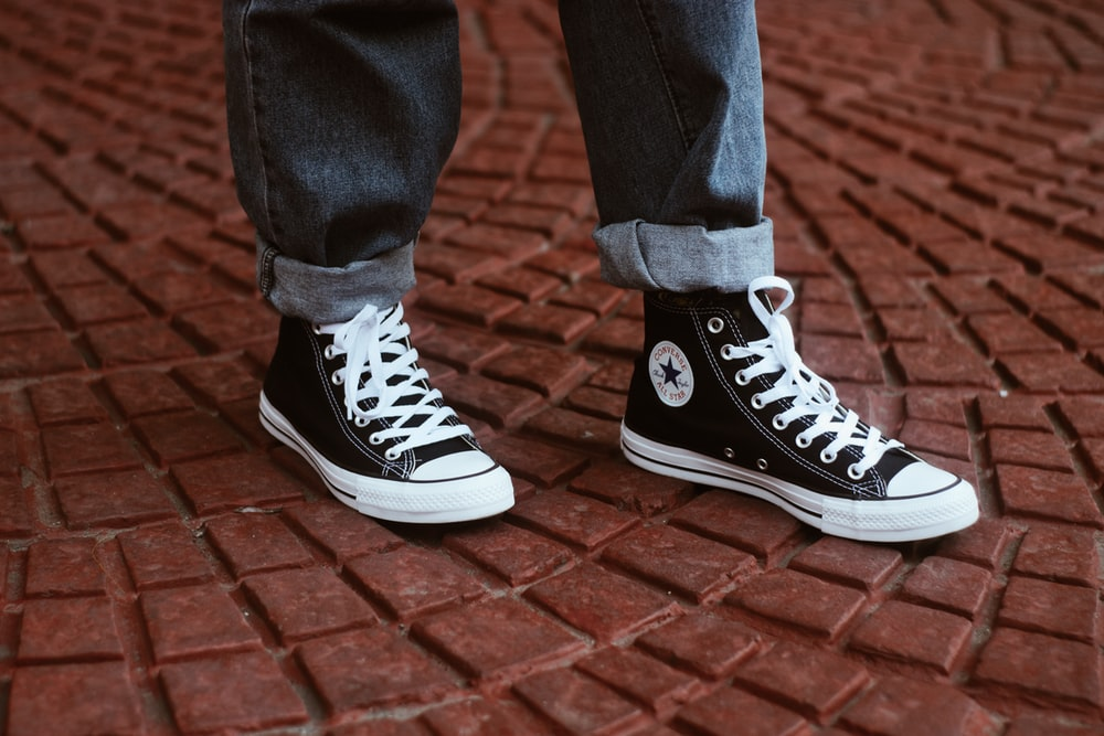 person showing pair of Converse All-Star high tops