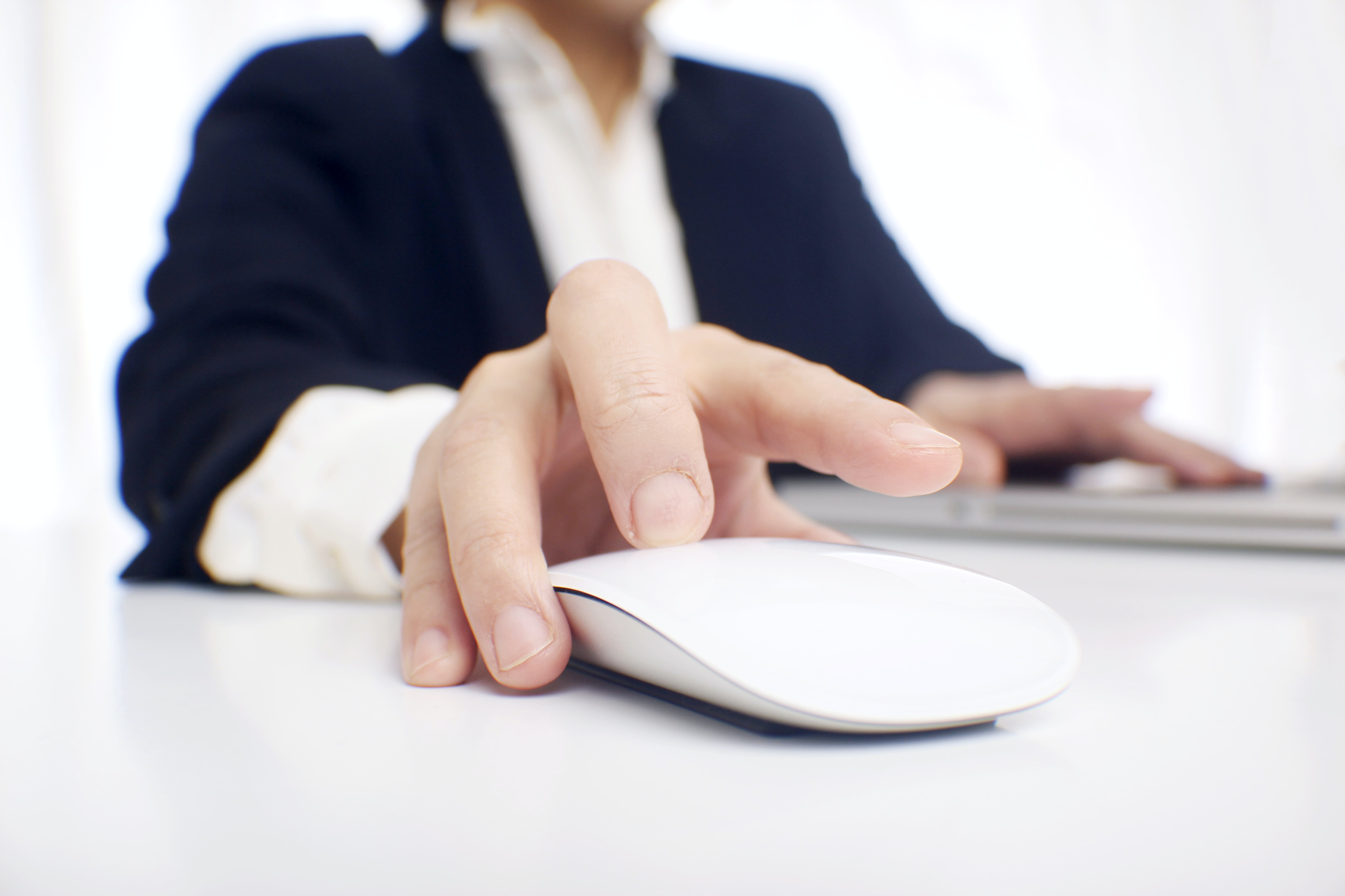 person using white Apple Magic mouse on top of table