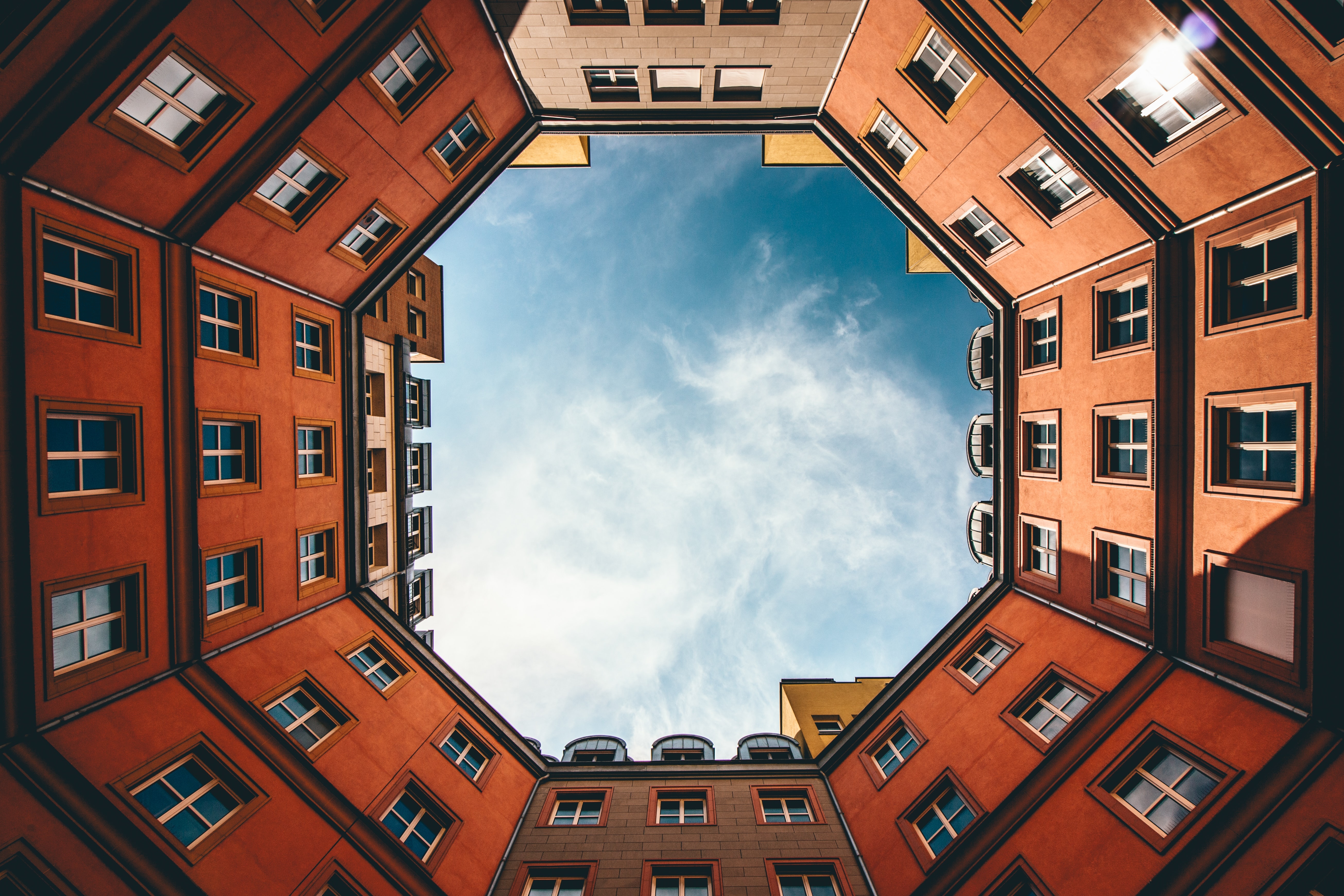 low-angle photography of hexgonal orange and brown concrete building under white clouds and blue sky during daytime