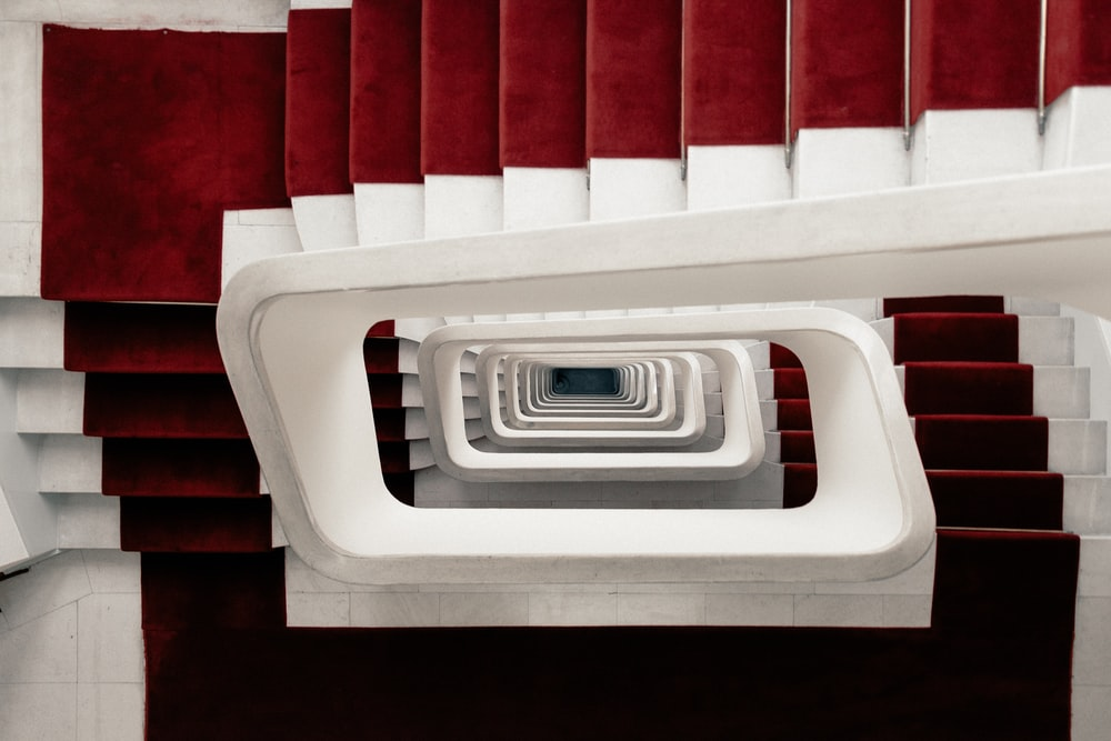 high-angle photo of spiral stairs with red carpet