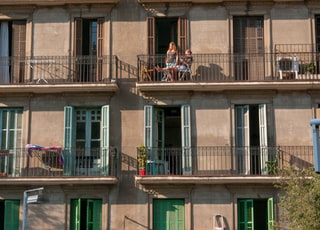 two man and woman on building's balcony during daytime