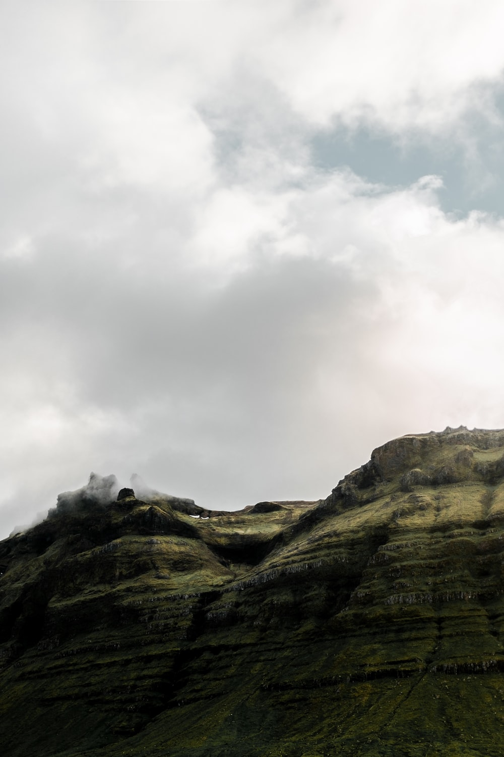 mountain under cloudy sky during daytime