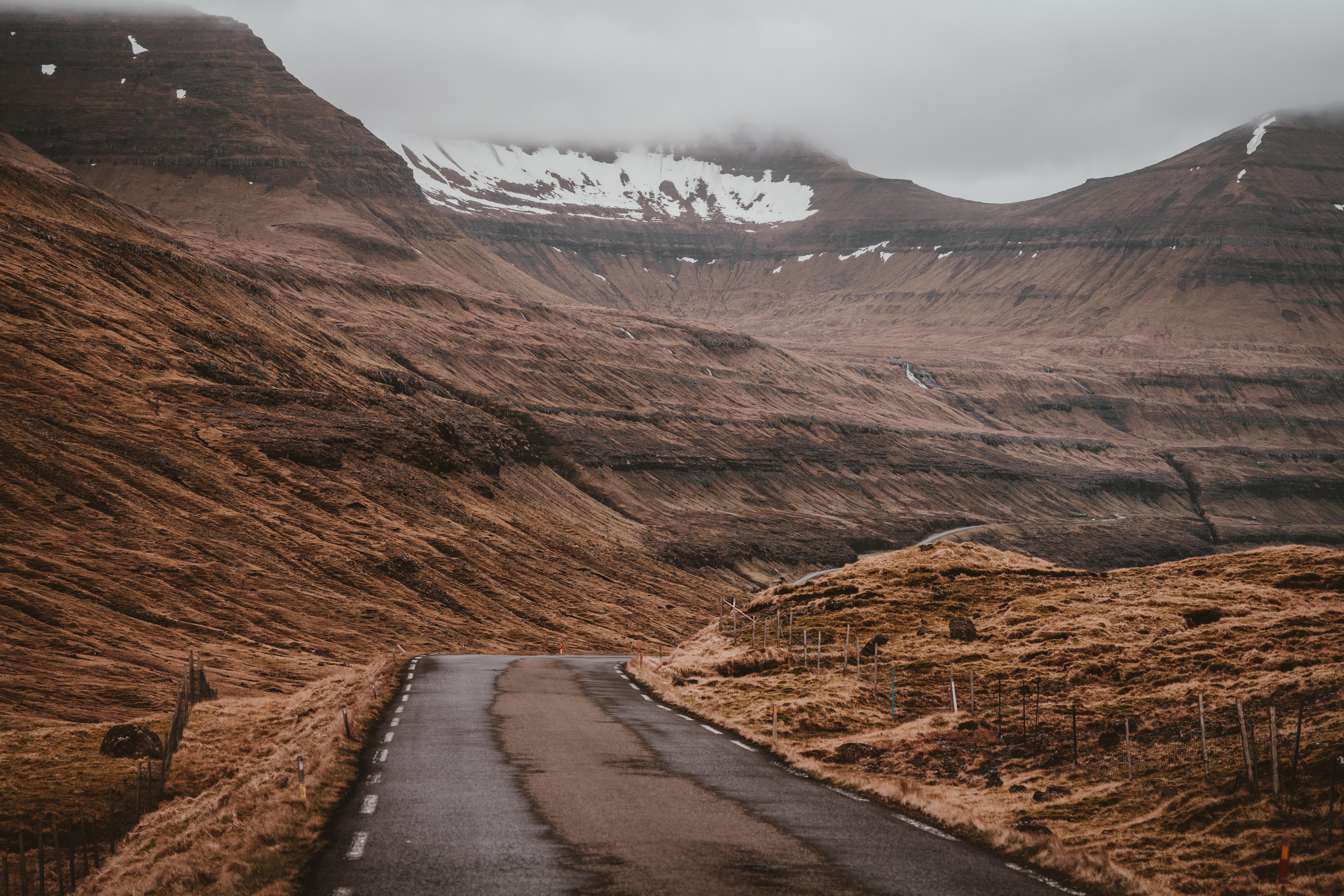 road in between brown mountains