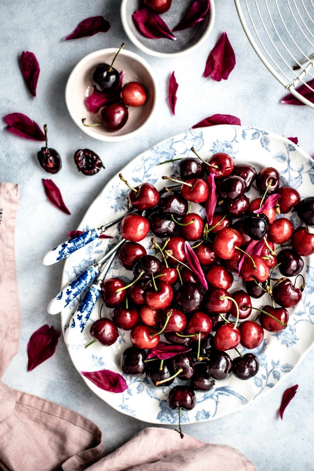 red cherry fruits on oval white and blue floral ceramic plate