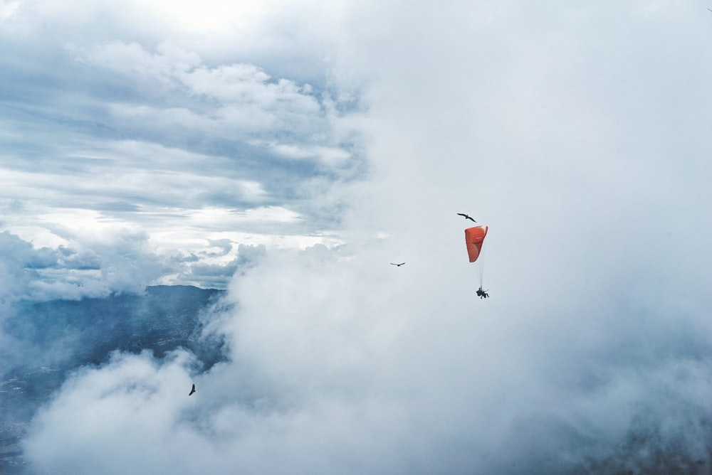 person paragliding surround by clouds
