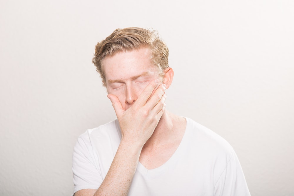 man covering his mouth, feeling frustrated