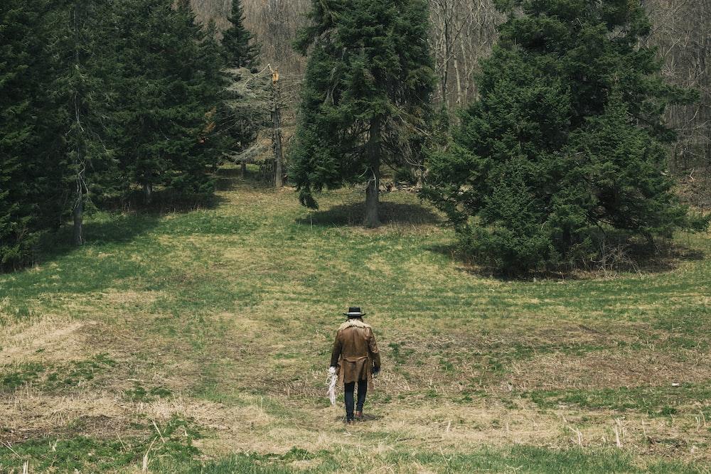 man standing on green grass field