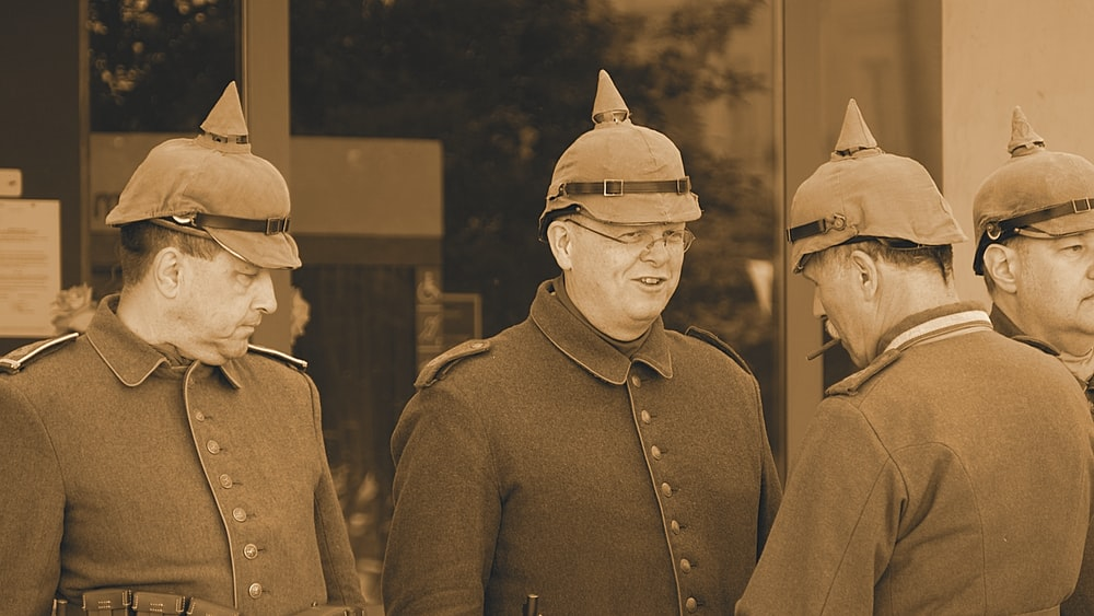four men wearing caps