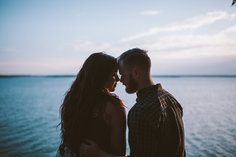 man and woman planning to kiss other near ocean