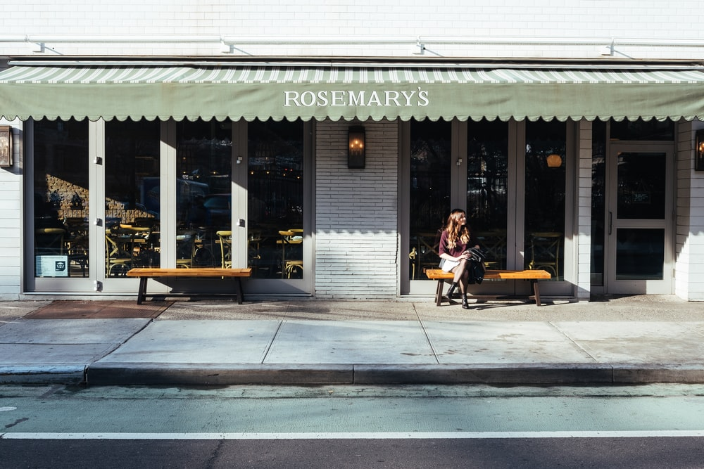 woman sitting in front of the store