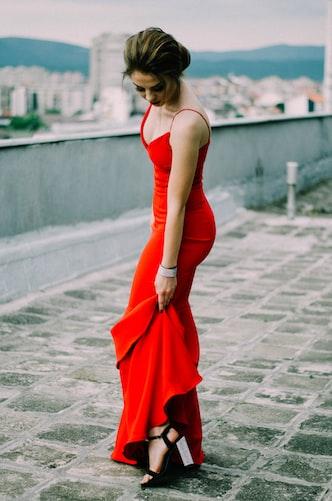 Une femme portant une robe rouge moulante.   Photo : Unsplash