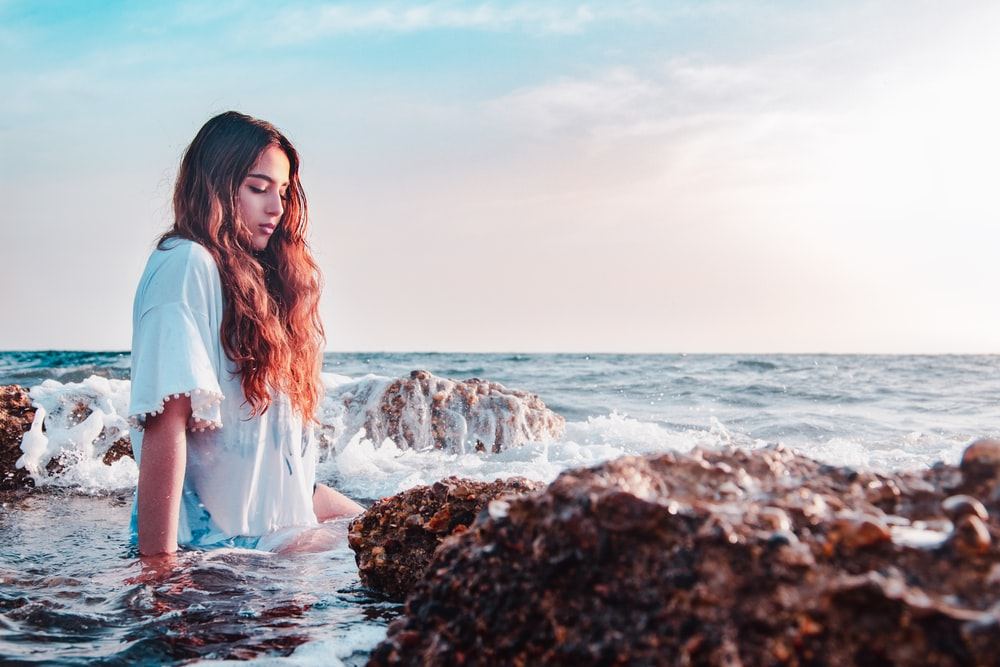 woman sitting at the rocky shore
