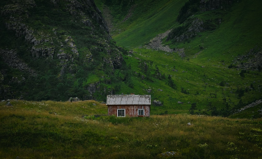 brown and white cabin on grass field beside green mountain