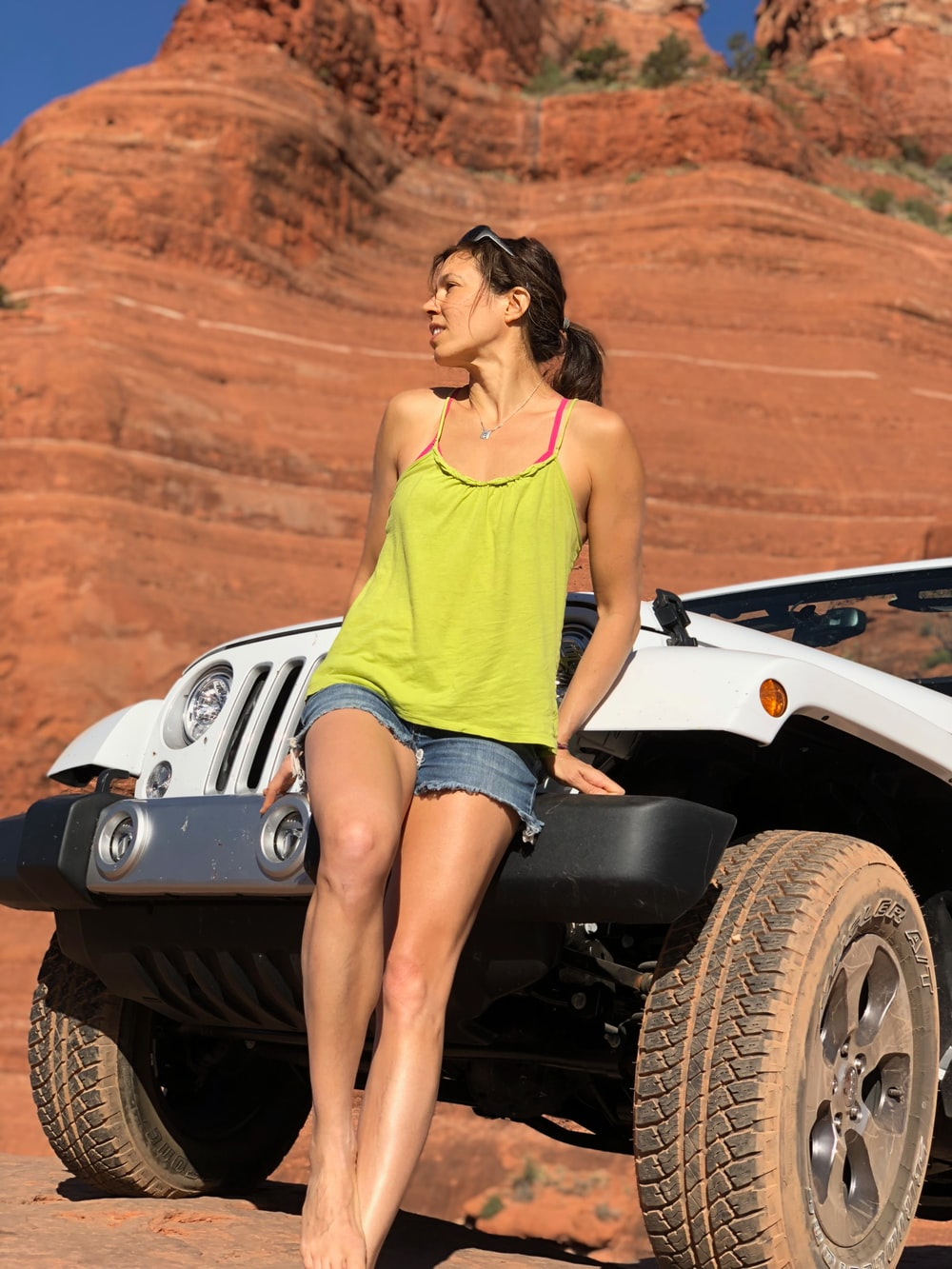 woman sitting on white Jeep Wrangler's front bumper