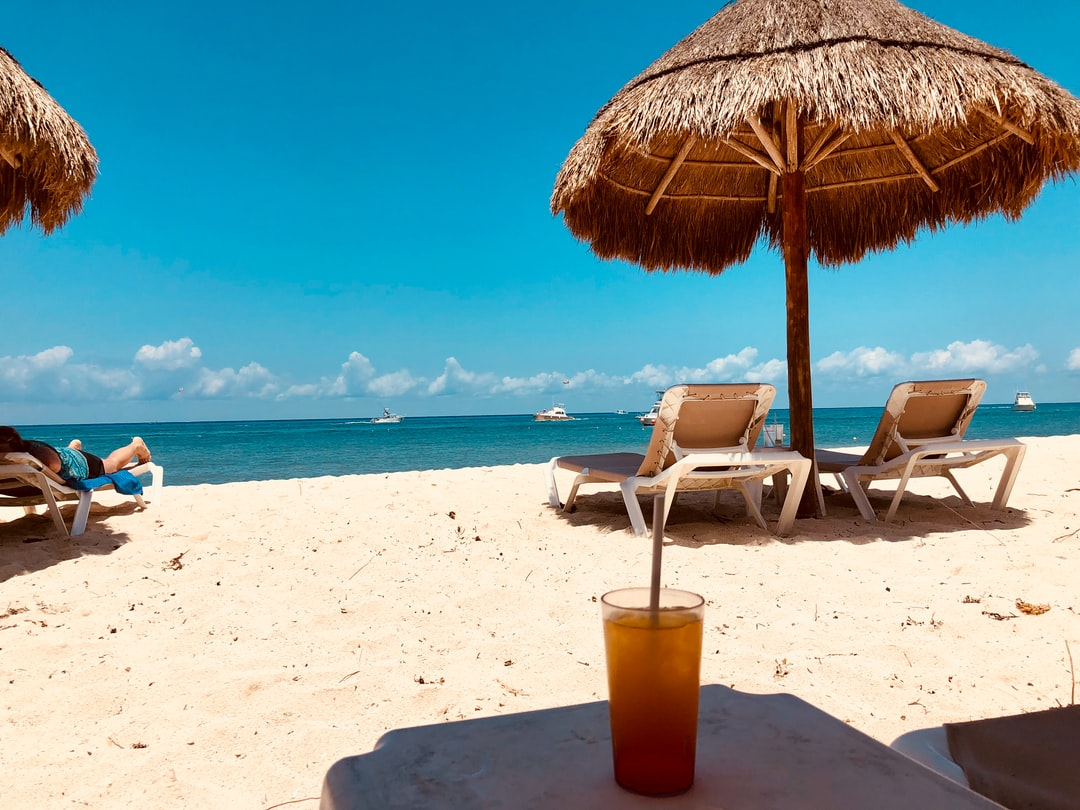 brown parasol and two beach chairs on beach sand in Nachi Cocom Beach Club Carretera Costera Sur Mexico