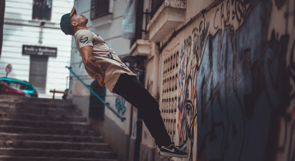 man jumping near wall