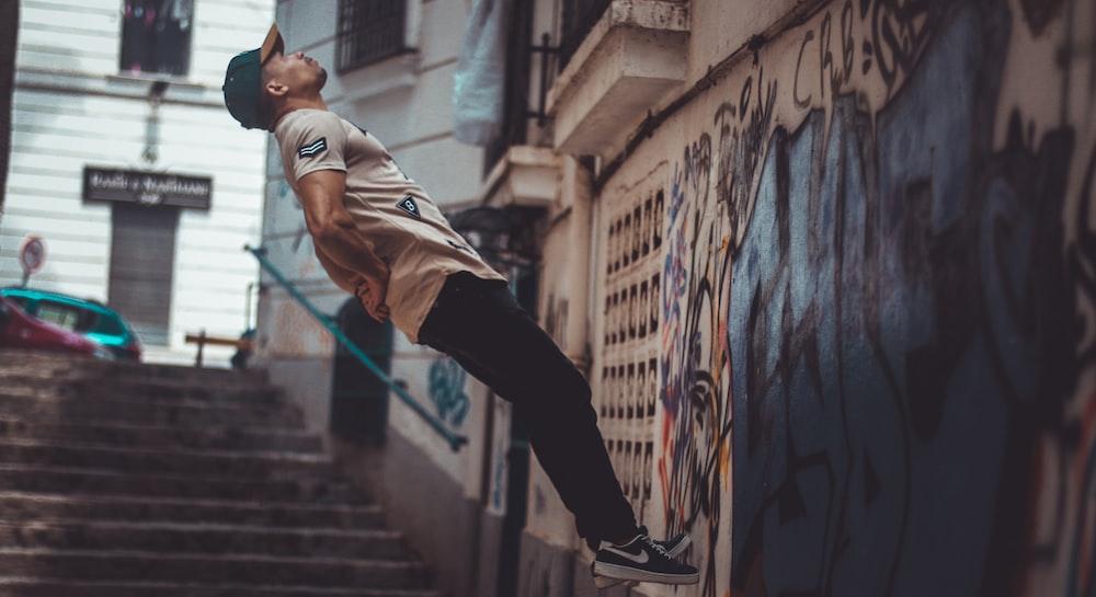 man jumping near wall