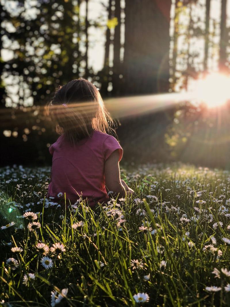 森の花に囲まれて座る子ども