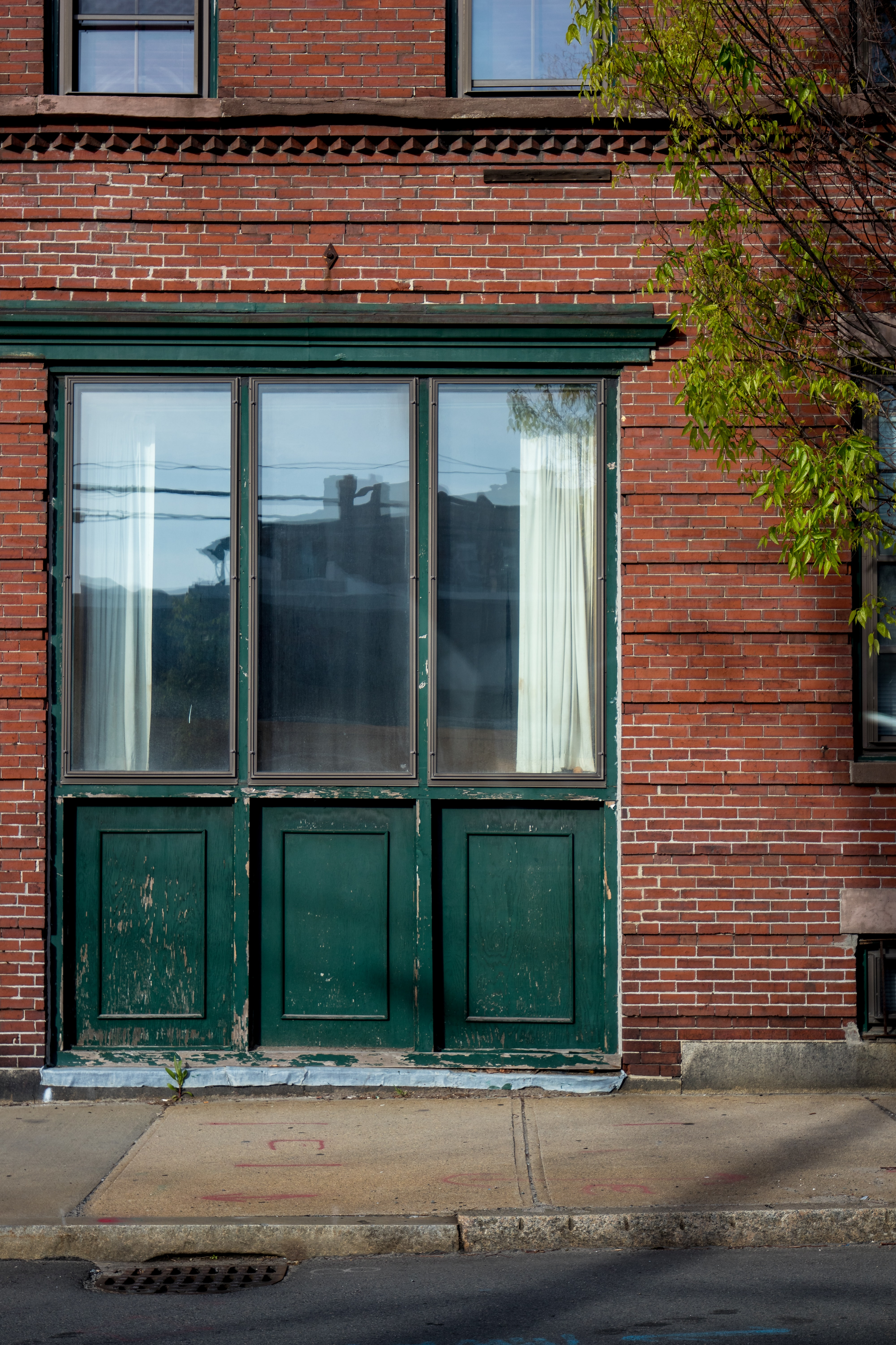 closed glass window with brick wall