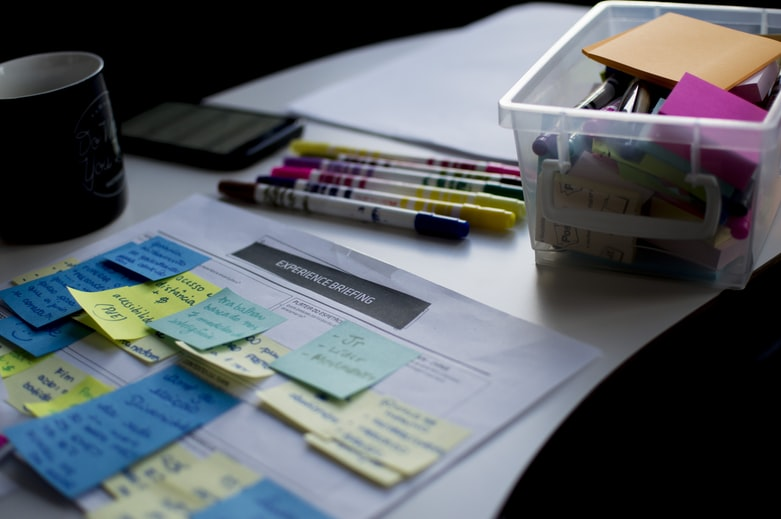 sticky notes on paper document beside pens and box