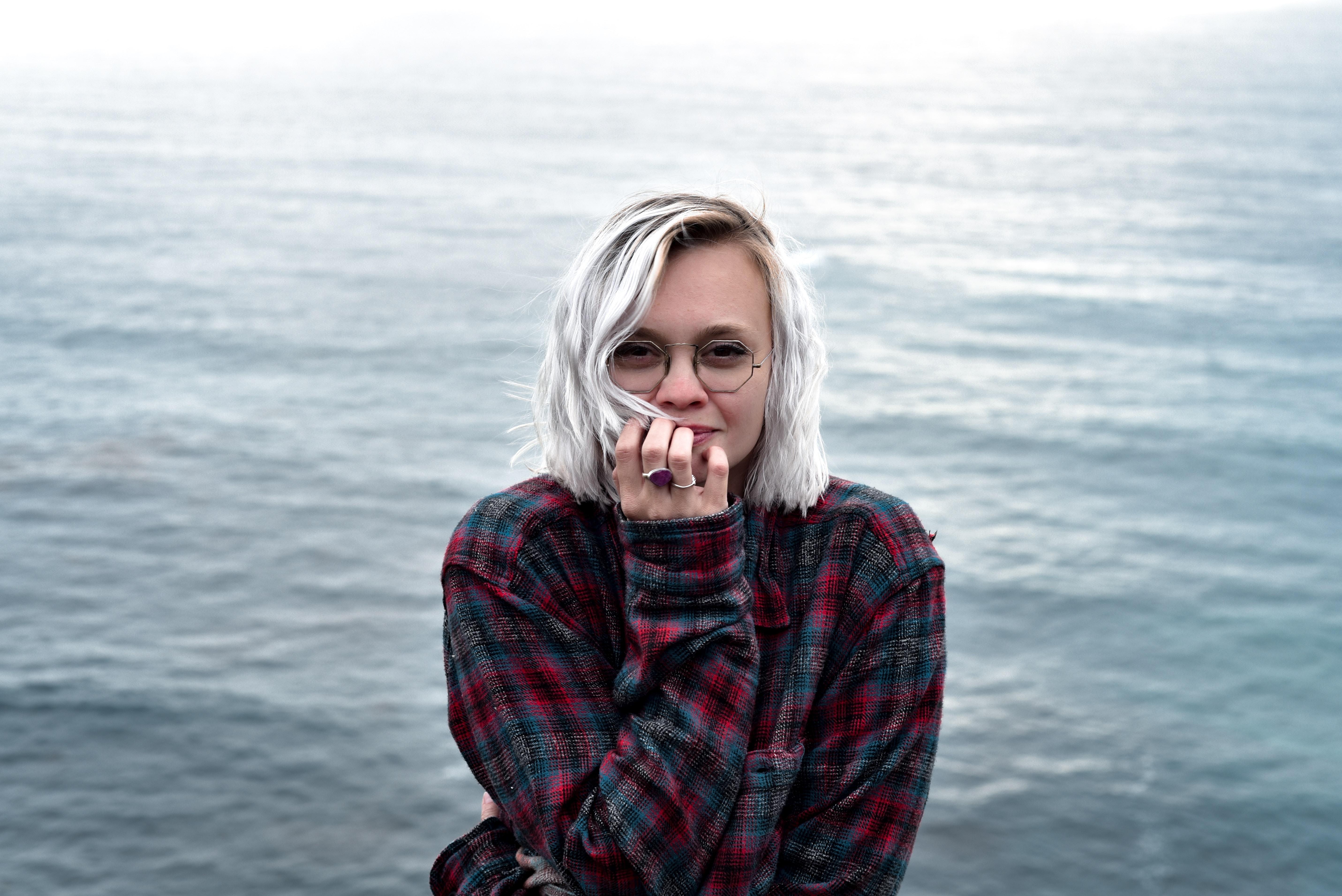 woman posing beside body of water