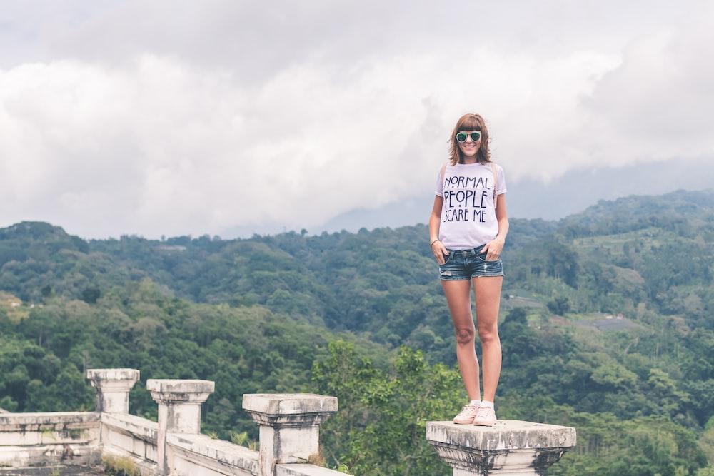 woman standing on concrete pillar