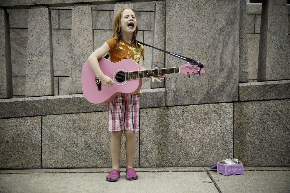 girl playing guitar near wall