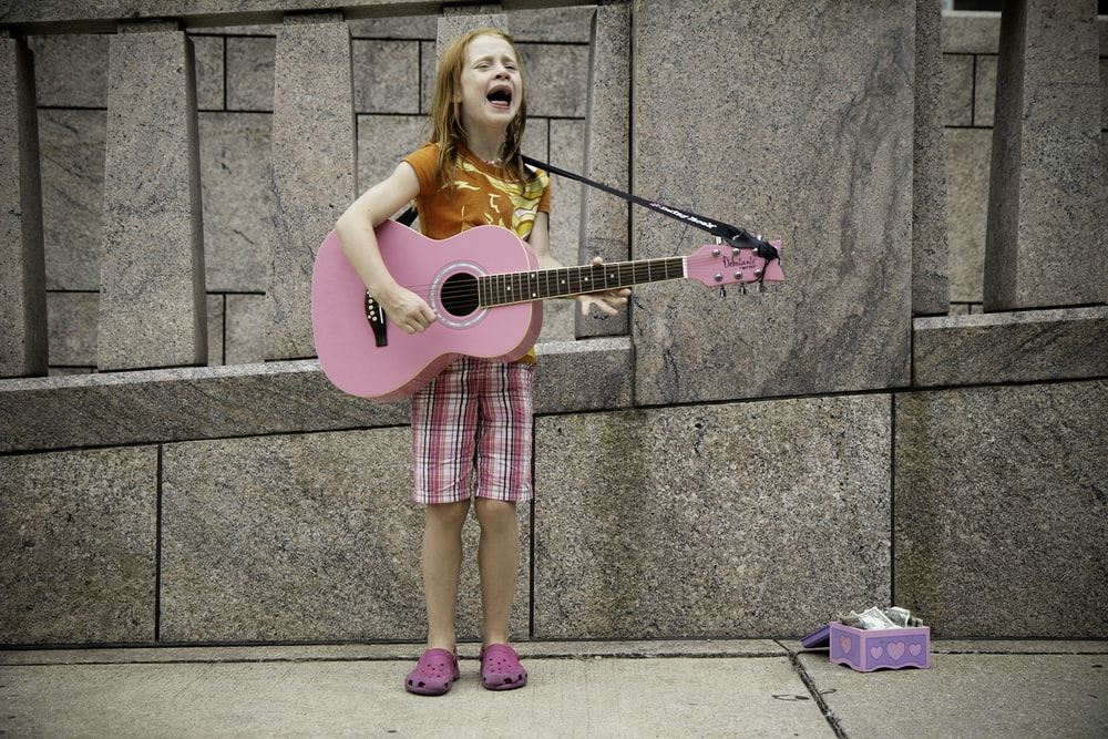 girl playing guitar near wall