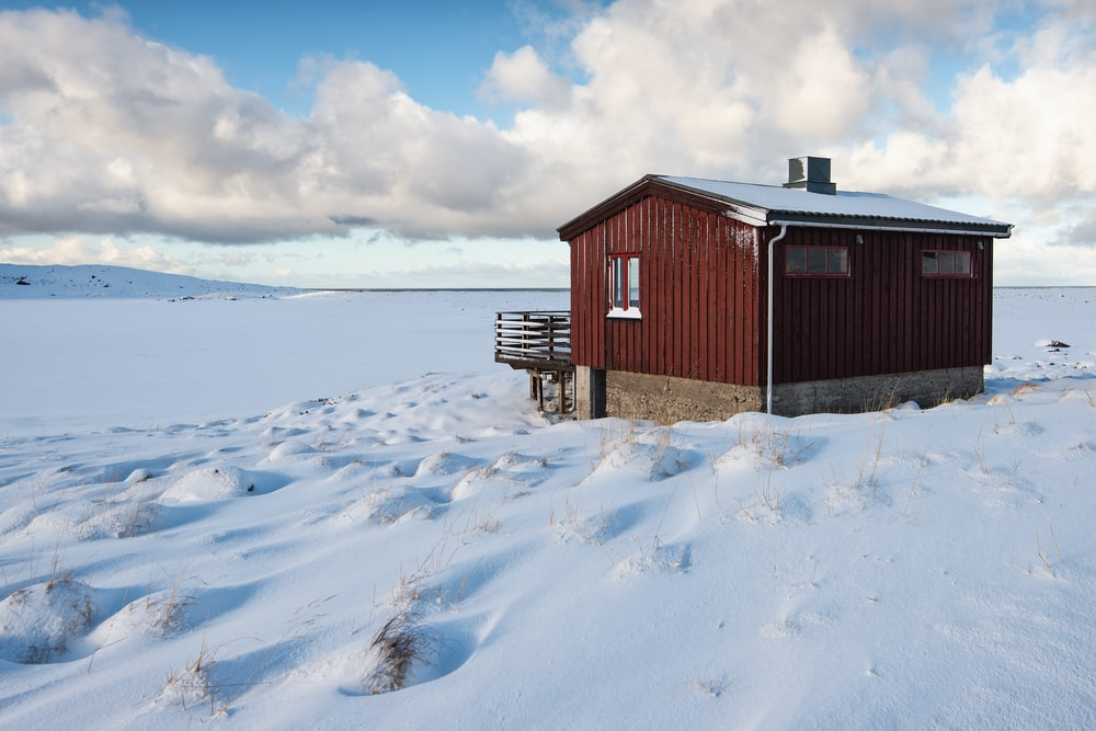 red and brown wooden cabin on field covered by snow at daytime