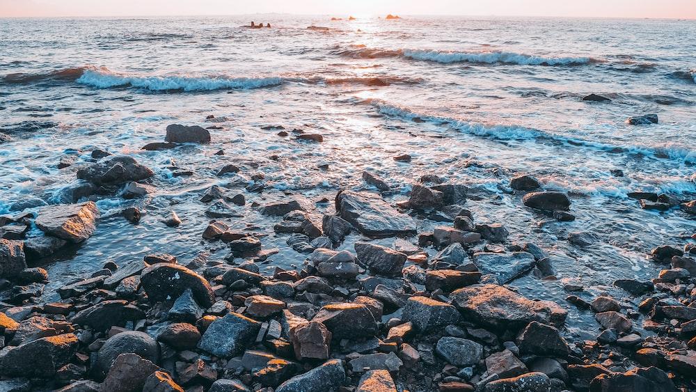 photo of body of water hitting brown rocks