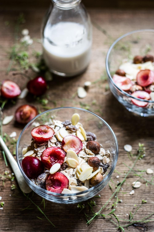 fruits in clear glass bowl beside milk bottle