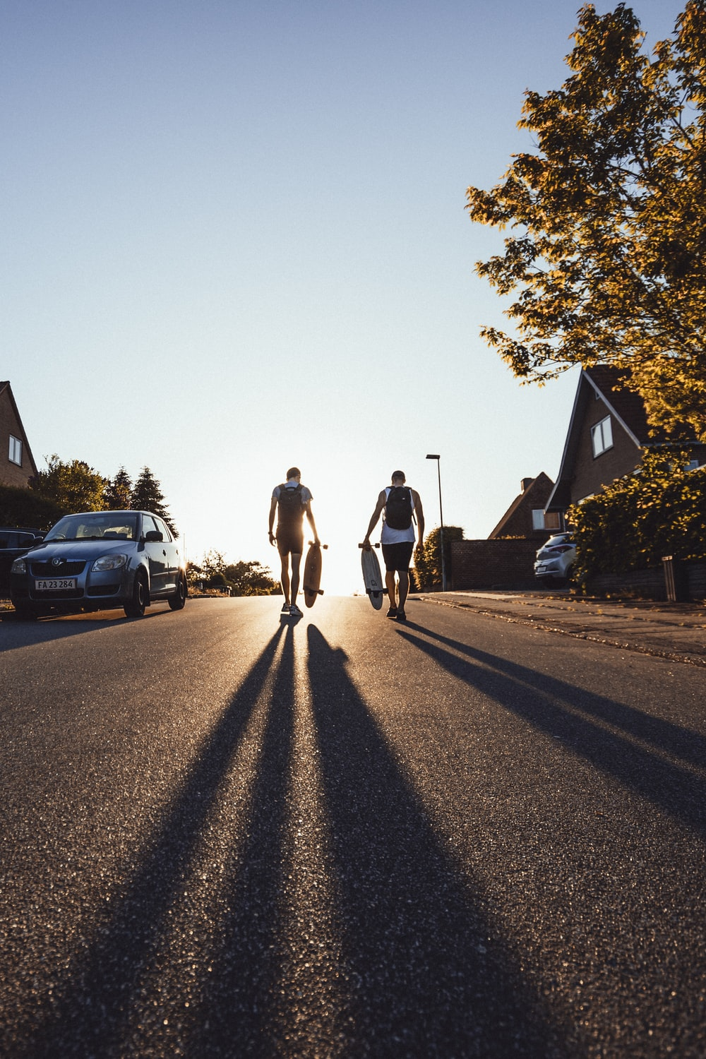 two men walking on road while holding longboard
