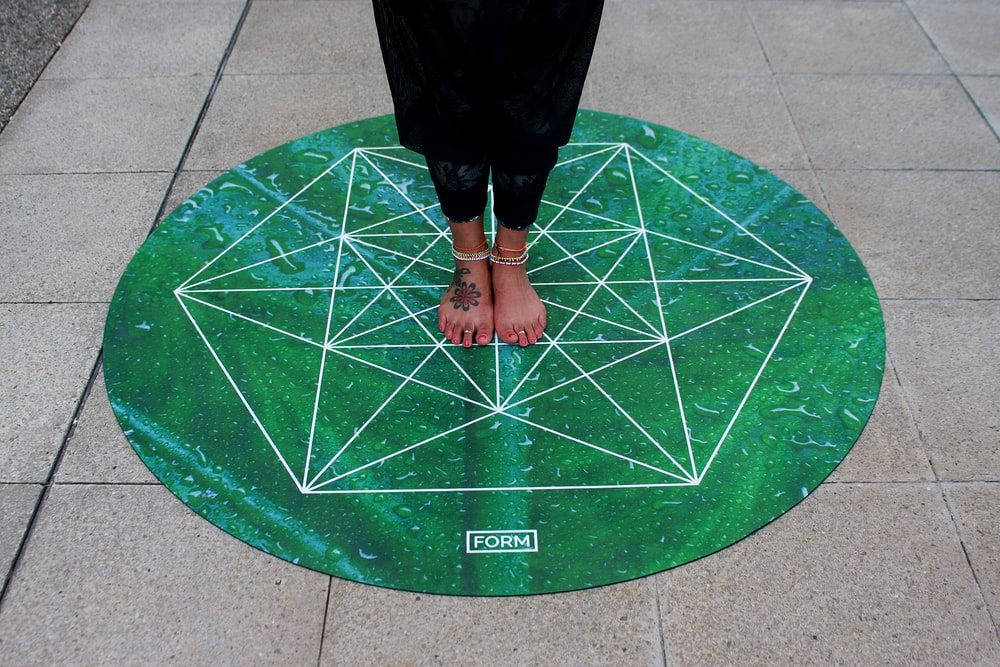 person standing on round green Form mat