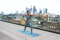woman stretching in top of building