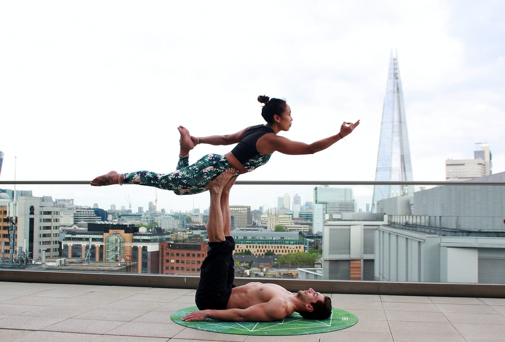 man and woman doing yoga pose