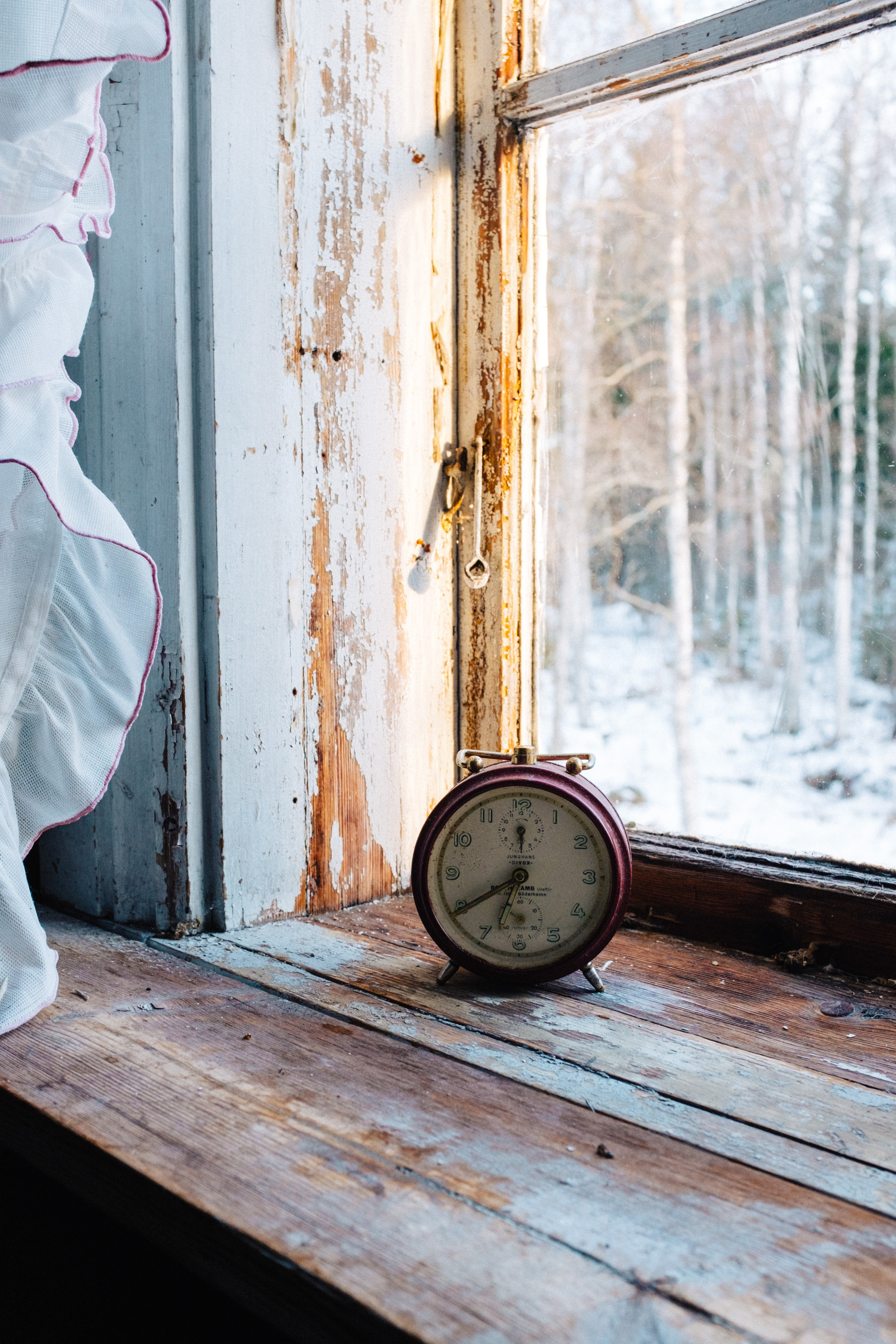 photo of red analog alarm clock beside window